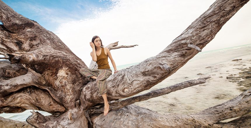 Pretty woman in alladin pants is relaxing on the giant roots. Tropical sea on the background.